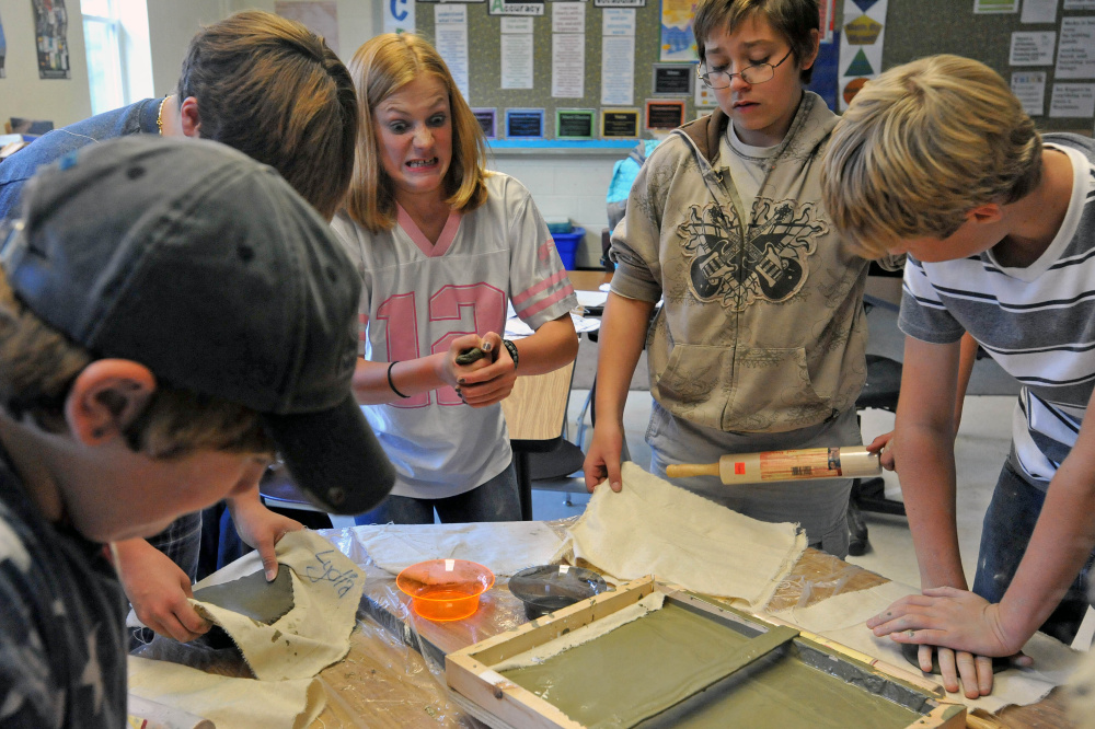 Katie Vanvliet, 13, center, grimaces as she molds a piece of clay during art class at the Cornville Regional Charter School on Wednesday. Every Wednesday for two hours students at the Cornville school get hands-on instruction from two artists and two musicians who visit students in groups.