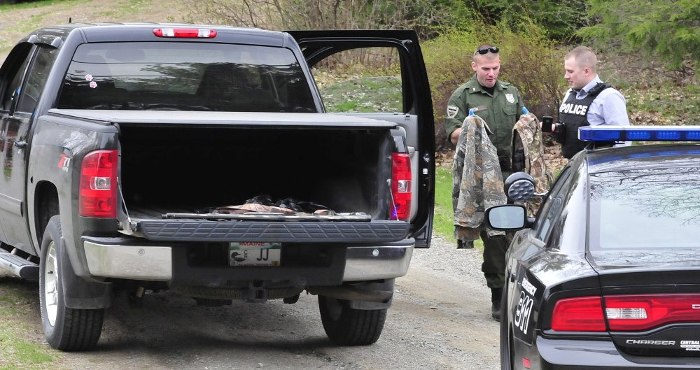 Game warden Dave Ross, left, and Winslow Detective Ryan McGowen look over turkey hunting gear belonging to the Janice and Reginald Jacques on May 5, after Janice Jacques accidentally shot Reginald while turkey hunting. Janice Jacques pleaded guilty to misdemeanor charges last month.