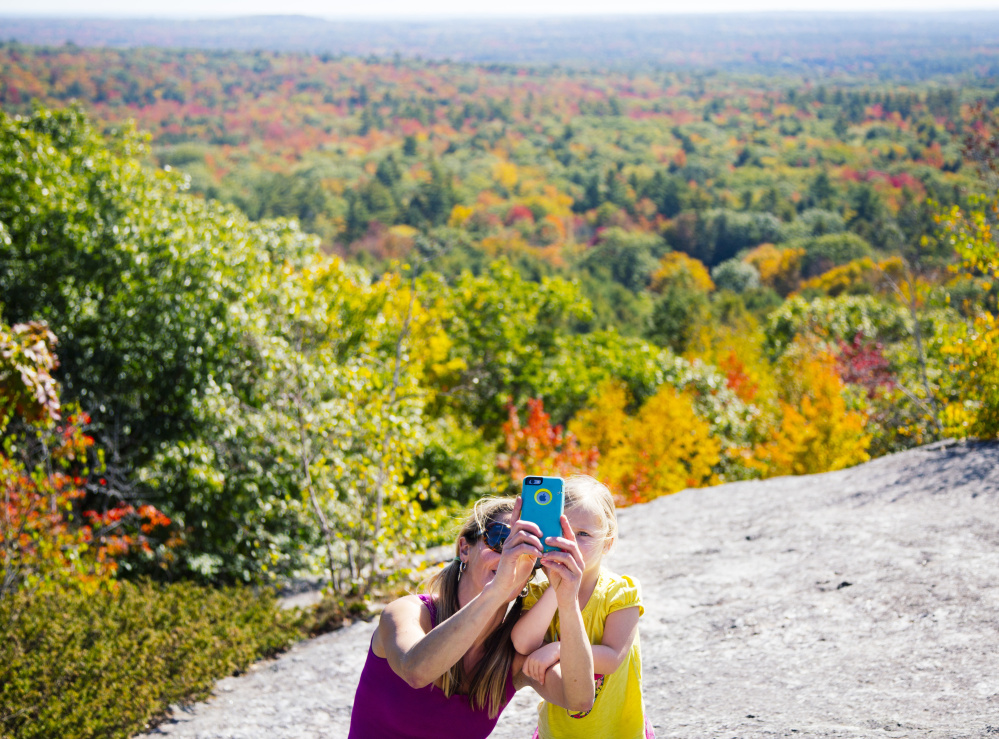 Kristin Brennan, left, takes a selfie with Pearl Brennan, 3 years old, both from the Portland area, at the summit of Bradbury Mountain at Bradbury Mountain State Park in Pownal on Monday.