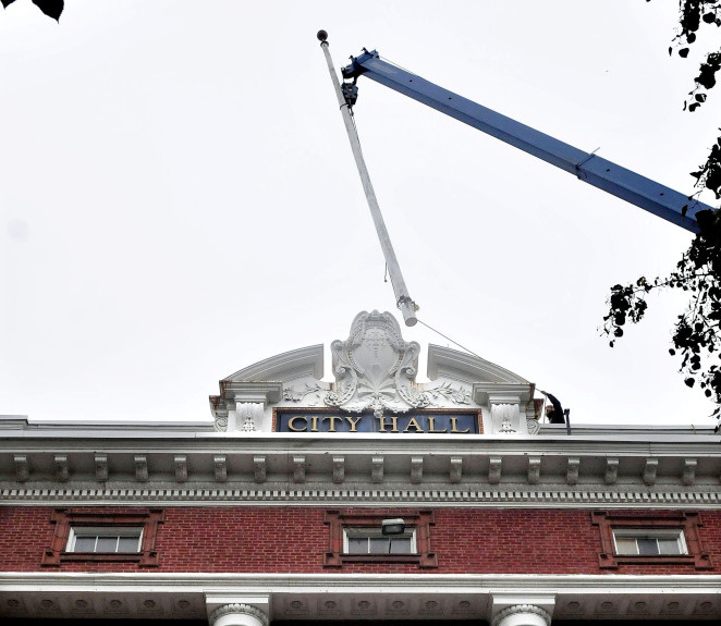 A worker holding a rope guides the Waterville City Hall 100-year-old flagpole away from the roof as a crane operator lowers it to the ground on Tuesday. The workers also removed 4,000 bricks. The work was in anticipation of next year's roof replacement project.