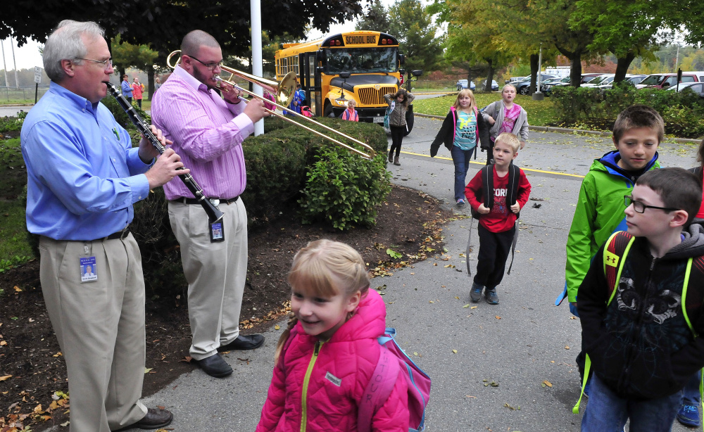 Benton Elementary School music teachers David Hoagland, left, and Josh Lund play as students get off the bus for school on Tuesday morning.