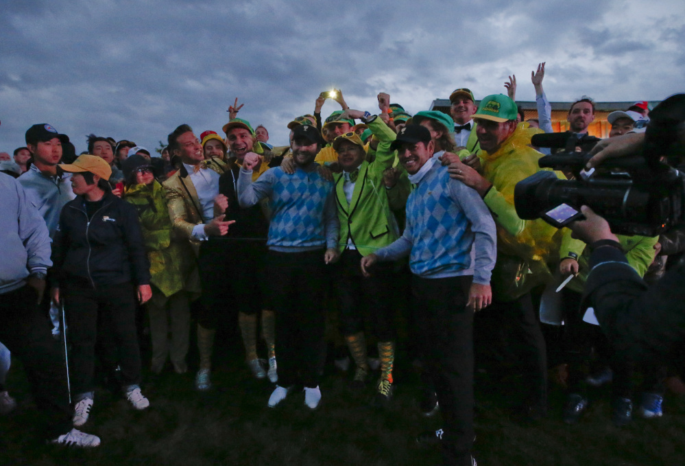 International team player's Branden Grace and Louis Oosthuizen are surrounded by fans after they won their four ball match in fading light at the Presidents Cup at the Jack Nicklaus Golf Club Korea in Incheon, South Korea on.