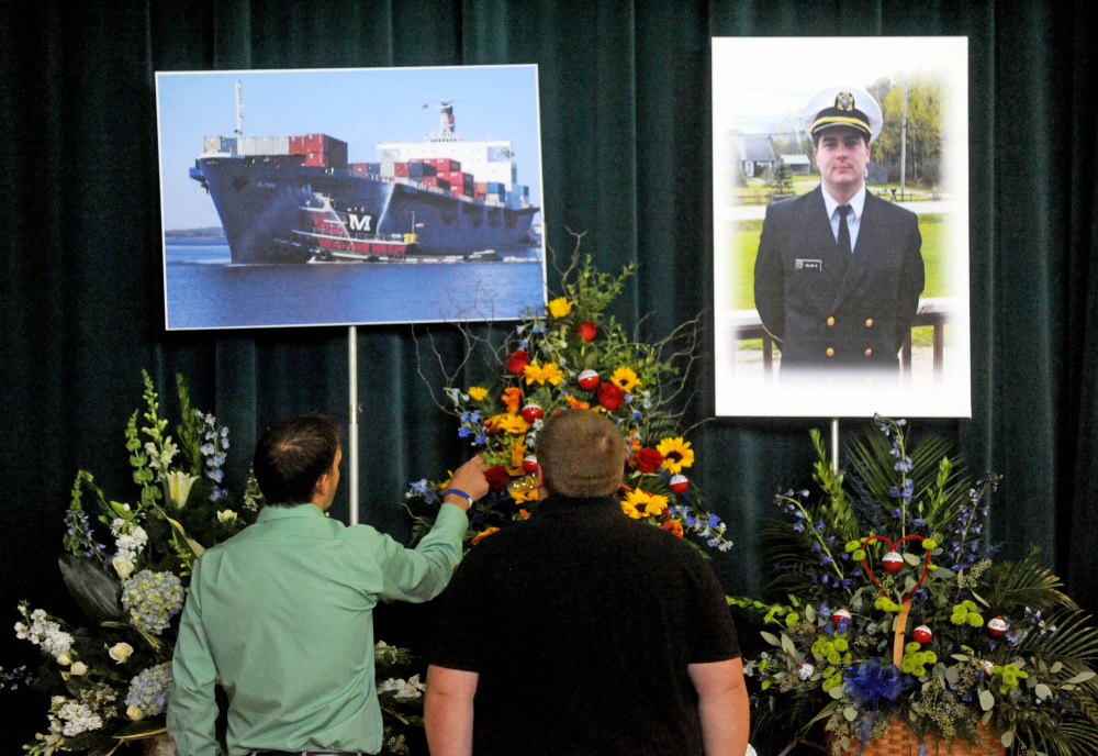 Friends and family pay their respects to a picture of Michael Holland and the cargo ship he worked on during a celebration of life at the Jay Community Building on Wednesday.