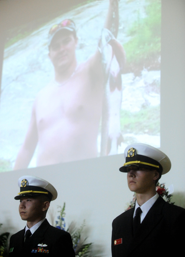 Members of the Coast Guard stand at attention as pictures of Michael Holland are displayed on the wall behind them during a celebration of Michael Holland's life at the Jay Community Building on Wednesday.