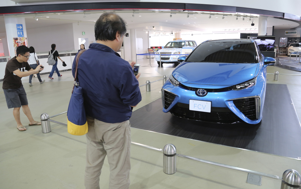 In this June 26, 2014 photo, visitors look at Toyota Motor Corp.'s new fuel cell vehicle (FCV) on display at a Toyota showroom in Tokyo. Toyota, under ambitious environmental targets, is aiming to sell hardly any regular gasoline vehicles by 2050, only hybrids and fuel cells, to radically reduce emissions.