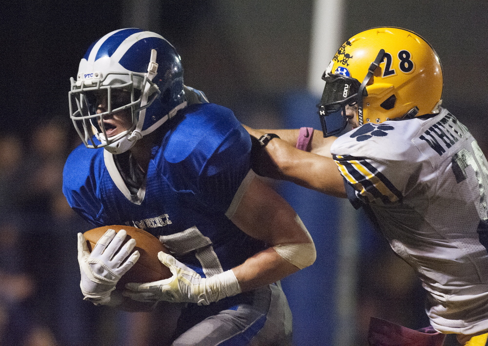 Lawrence running back Seth Powers fights off Mt. Blue's Christian Whitney to reach the end zone during a Pine Tree Conference Class B game this season.