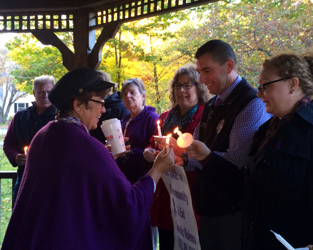 """Kathleen Dumont, left, of Kennebec Valley Behavioral Health, lights a candle for Somerset County Sheriff's Office domestic violence investigator Mike Pike, right, and others at a domestic violence awareness vigil Wednesday in Skowhegan. The vigil was part of a """"speak-out"""" event aiming to bring awareness to domestic violence during October, which is Domestic Violence Awareness Month."""