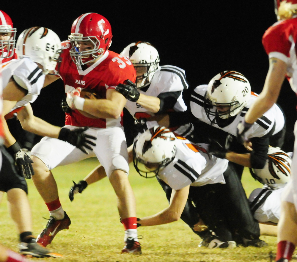 Cony running back Reid Shostak is surrounded by a swarming Skowhegan defense during a Pine Tree Conference B game last season at Alumni Field in Augusta.