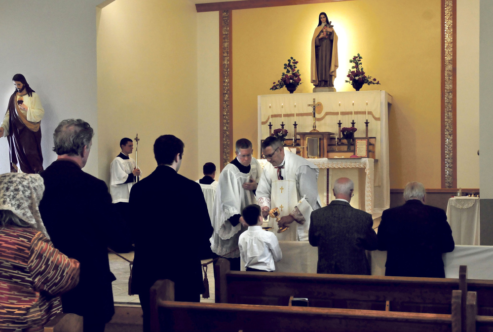 Bishop Mark Pivarunas gives Communion to Anthony Isgro, son of Waterville Mayor Nick Isgro, during a blessing at the St. Theresa's Church in Oakland on Thursday.