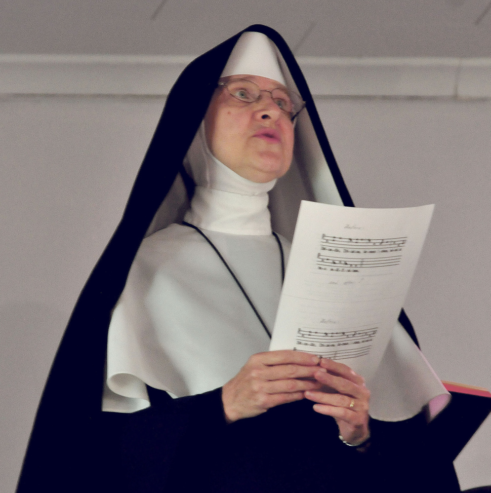 A nun sings hymns during a blessing of the St. Theresa's Church in Oakland on Thursday.