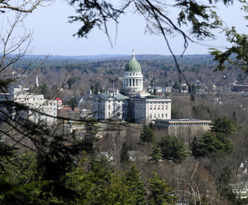The State House complex appears through trees at the top of Augusta's Howard Hill during a walking tour of the land on April 18. The wooded hill forms a backdrop to the State House.