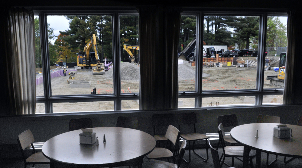Construction work on the new dining hall is seen framed through windows of Masterman Union, the school's current dining hall, on Friday at Kents Hill School in Readfield.