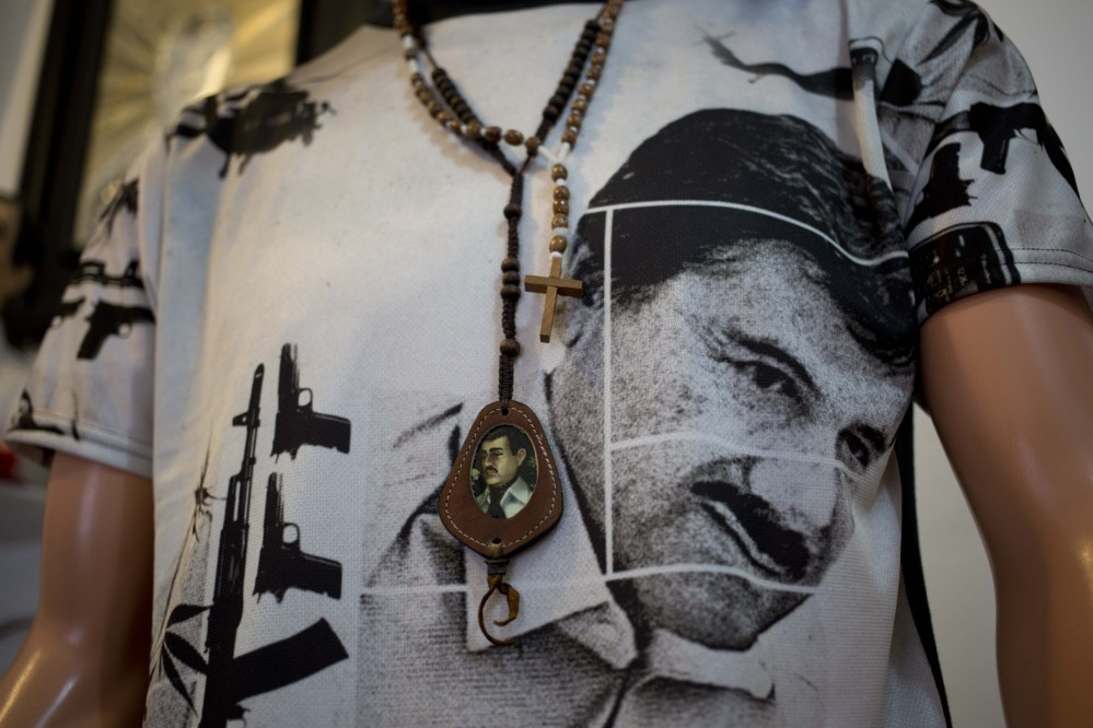 """A T-shirt of fugitive Mexican drug lord Joaquin """"El Chapo"""" Guzman covers a mannequin representing Jesus Malverde, known in Mexico as the """"Saint"""" of drug traffickers, inside the shrine of a faith healer in Mexico City, Friday."""