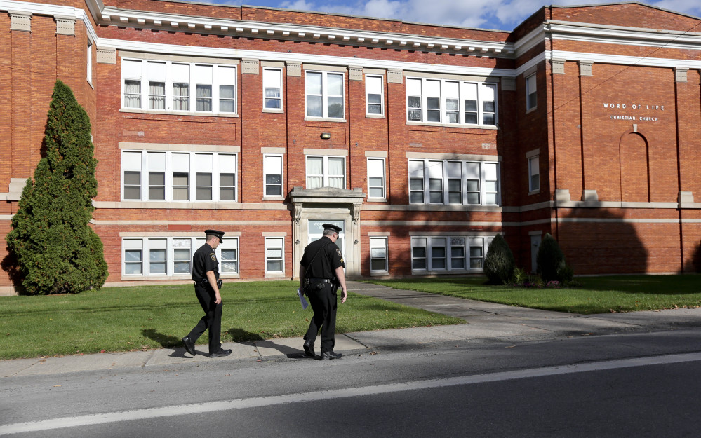 Police walk outside the Word of Life church on Thursday in New Hartford, N.Y.