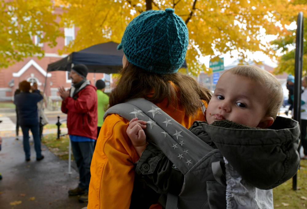 Doug Saunders, right center, addresses the crowd Saturday in Farmington before a fundraising walk hosted by the Franklin County Children's Task Force to support child-abuse prevention programs as Sarah Reynolds holds her son Fletcher, 15 months, on her back.