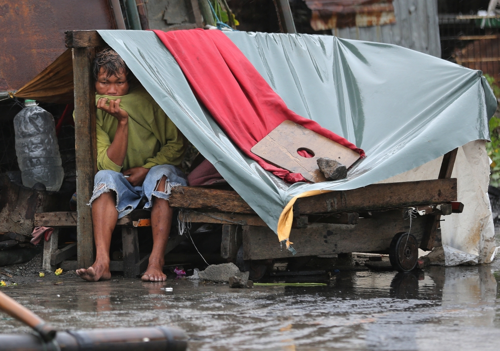 A Filipino man sits inside his makeshift home as strong winds and rains caused by Typhoon Koppu hits the coastal town of Navotas, north of Manila, Philippines on Sunday.