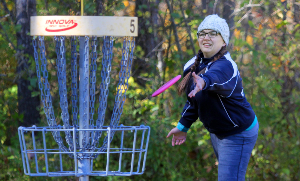 Megan Norton of New Gloucester tosses her disc toward the basket on No. 5 during the 2nd annual Porcupine Ridge PDGA Open at Porcupine Ridge on Sunday in Augusta.