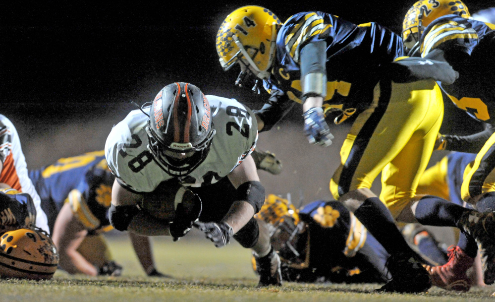 Staff photo by Michael G. Seamans   Brunswick's Will Bessey (28) dives for extra rushing yards during a Pine Tree Conference Class B game last Friday night against Mt. Blue. The Dragons can wrap up the No. 1 seed with a victory this Friday against winless Nokomis.