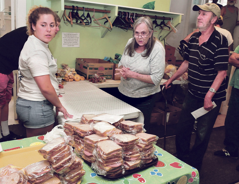 Staff file photo by David Leaming Volunteer and member of the Winslow High School Honor Society Meg Nadeau assists Linda Provencher and John Roy with food they selected at the Evening Sandwich program in July. The program, held daily at the Universalist Unitarian Church in Waterville, will be recognized with a proclamation at Tuesday's City Council meeting.