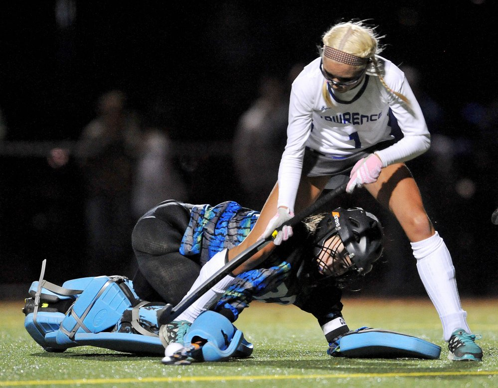 Staff photo by Michael G. Seamans   Lawrence junior forward Hallee Parlin (1) tries to get control of the ball from Old Town goalie Corinne Saucier during the second half of a Class B North quarterfinal game Tuesday night at Thomas College.