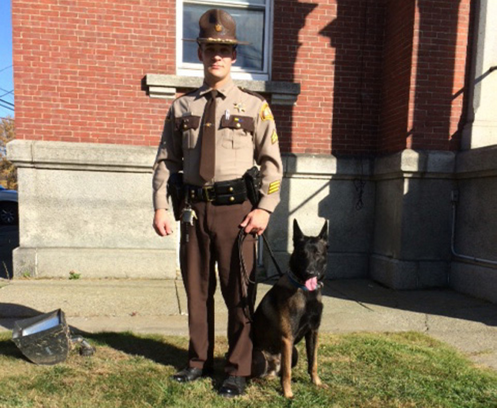 Cpl David Cole of the Somerset County Sheriff's Department poses Wednesday with the county's new patrol dog, 15-month old Kojo, a Belgian malinois. Purchase of the dog was approved Wednesday by county commissioners.