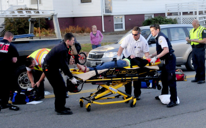 An injured teenager is carried to an ambulance after she ran into an SUV while crossing Silver Street in Waterville on Wednesday. The girl, who was taken to Inland Hospital, ran out into the street from between two vehicles that were stopped at a red light, police and witnesses said.
