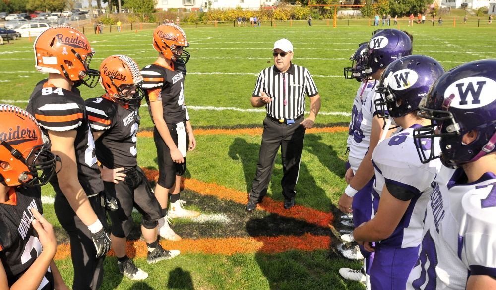 Members of the Waterville and Winslow football teams get ready for the coin toss before the annual Battle of the Bridge last season in Winslow.