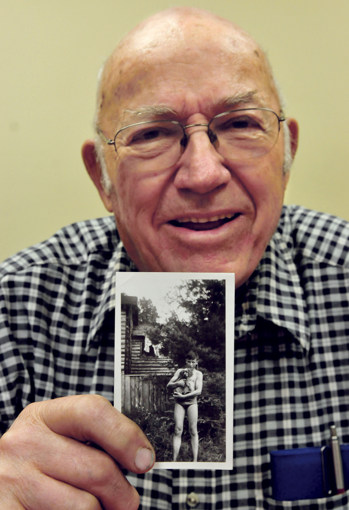 Robert McQuillan holds a photo taken of him in 1942, when he and family owned a cottage in Sidney on Messalonskee Lake, a few camps down from Charles Terry's family. He and his brother, John, remember Terry as a troublemaker. Terry was later convicted of murder.