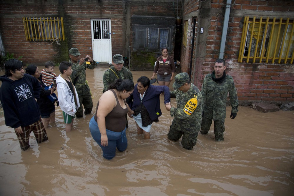Soldiers help a woman leave her flooded house in in Zoatlan, Nayarit state, about 100 miles northwest of Guadalajara,  Mexico. Hurricane Patricia made landfall Friday on a sparsely populated stretch of Mexico's Pacific coast as a Category 5 storm but weakened to a tropical storm when it ran into mountains. It dumped torrential rains that authorities warned could cause deadly floods and mudslides. (AP Photo/Eduardo Verdugo)