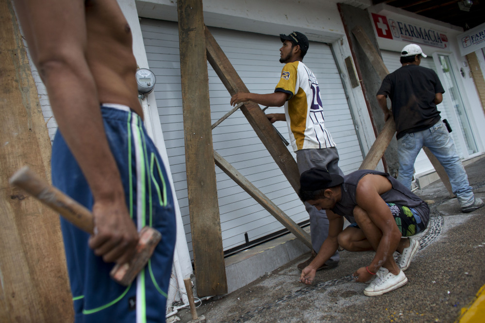 Men remove protective wood beams from the front of a business the morning after Hurricane Patricia passed further south sparing Puerto Vallarta, Mexico, on Saturday.