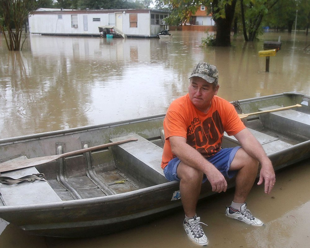 J.B. Neckar, waits in his boat as waters rise near Downsville, Texas, Saturday, Oct. 24, 2015. Heavy rains have forced parts of the Brazos River out of its banks and endangering homes located in the small community just outside of Waco, Texas, according to the Waco Tribune Herald. (Jerry Larson/Waco Tribune Herald, via AP) MANDATORY CREDIT