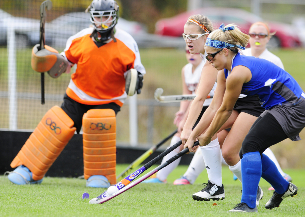 Staff photo by Joe Phelan   Gardiner goalie Kaylin Mansir, left, watches as teammate Mikayla Bourassa tries to stop Lawrence forward Domi Lewis during a Class B North semifinal game Saturday afternoon in Gardiner.