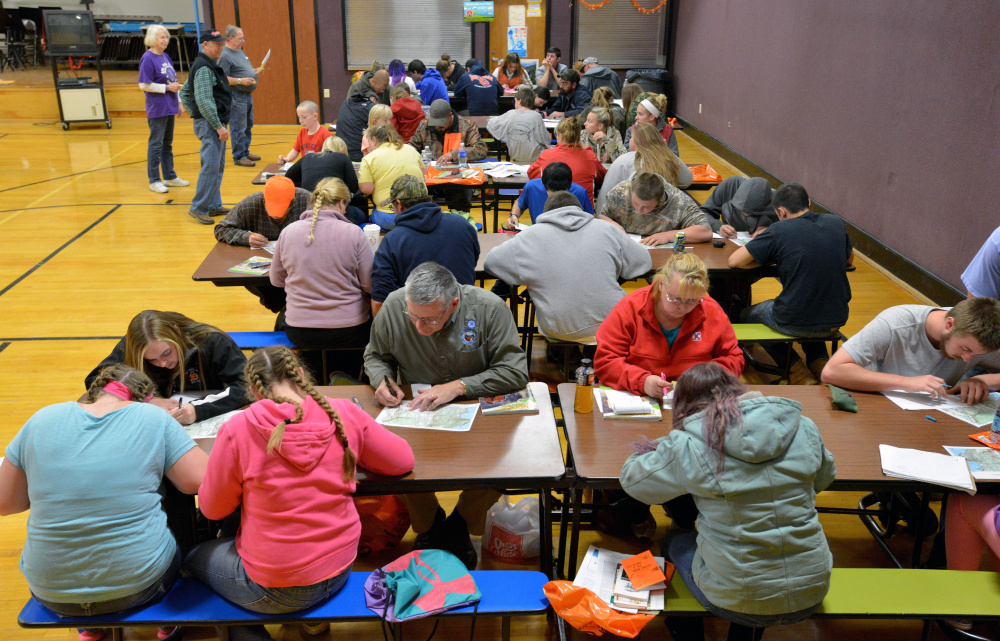 People participating in a hunter safety course Wednesday at Harmony Elementary School learn the finer points of map and compass use.