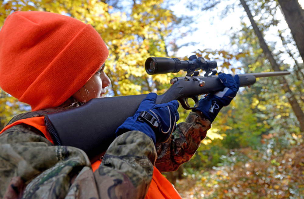 Jadee Garcia, 11, looks through the scope on her .22-caliber Magnum rifle Saturday on her first day of hunting in Harmony.