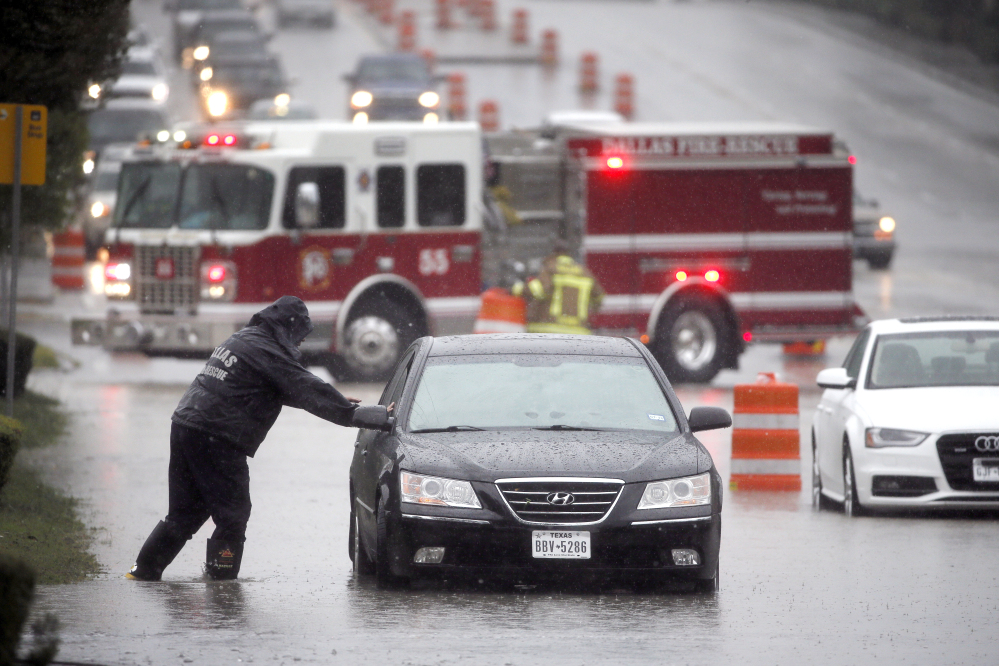 A Dalls Fire Rescue responder makes his way over to a stalled vehicle to check on the driver still inside on Friday in Dallas.