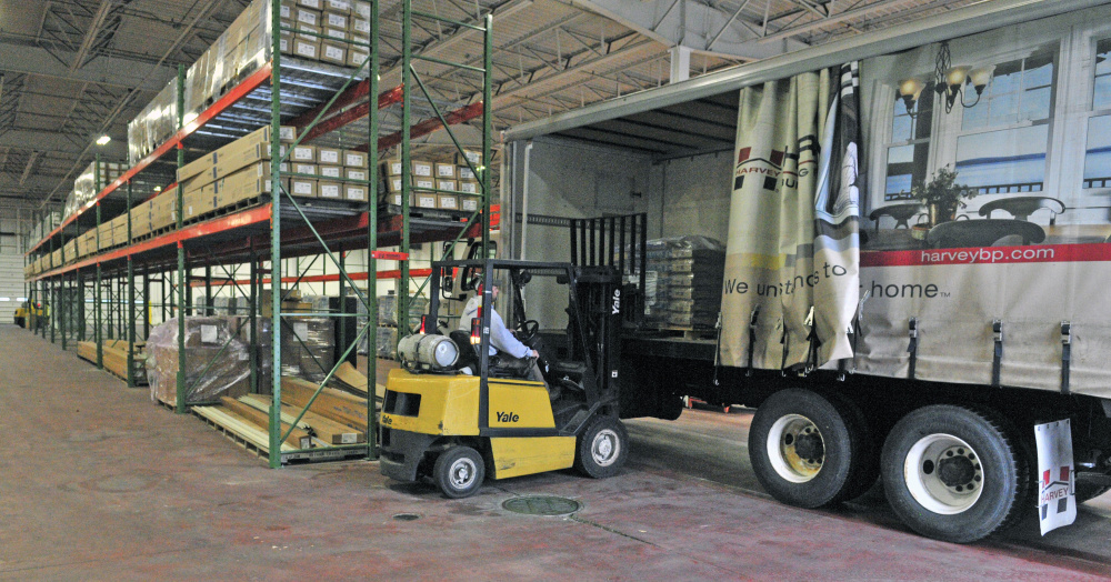 Warehouse manager Jake Dube use a forklift to load a delivery truck Thursday at the Harvey Building Products warehouse on Anthony Avenue in Augusta.