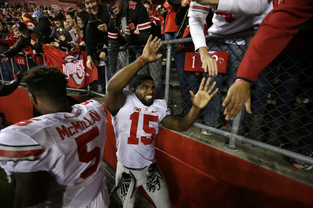 Ohio State running back Ezekiel Elliott (15) and linebacker Raekwon McMillan (5) greet fans on the field after a game against Rutgers on Saturday in Piscataway, N.J. Ohio State won 49-7 and remains No. 1 in the AP poll.