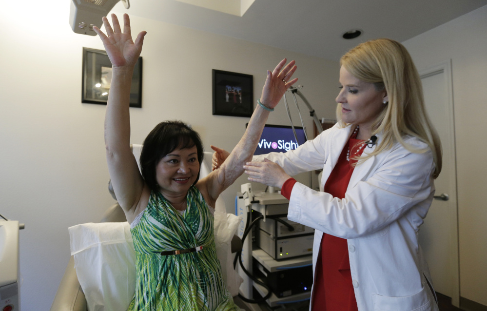 Dr. Jill Waibel examines Kim Phuc in Miami before the first of several laser treatments to reduce pain from burns Phuc received more than 40 years ago when her village in Vietnam was hit by an errant napalm bomb.