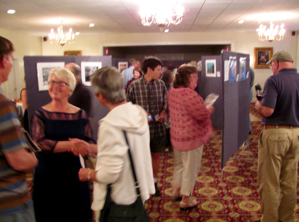Linda Sikes, chairperson for the Western Mountain Photography Show, and sponsored by the Rangeley Friends of the Arts, is shown in lower left greeting photography enthusiasts at the Awards Reception.