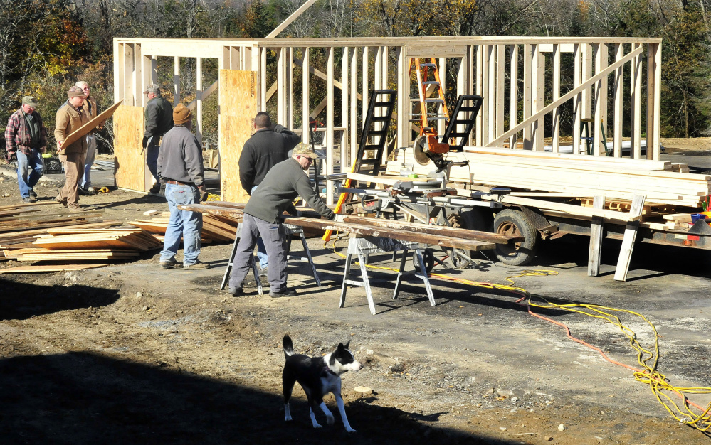 Homeowner Jeff Chadbourne, center, watches as friends and volunteers help build a new barn at his farm in Harmony on Monday after fire destroyed the old barn last week, killing several farm animals.