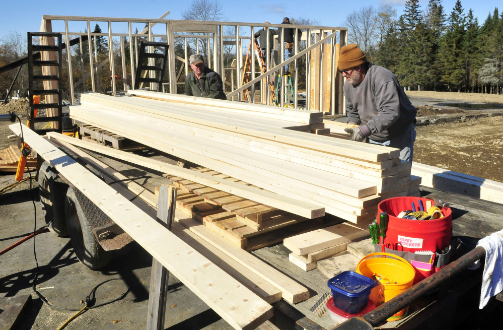 Homeowner Jeff Chadbourne, right, and friend Rick Clowry and other volunteers help build a new barn at the farm in Harmony on Monday.