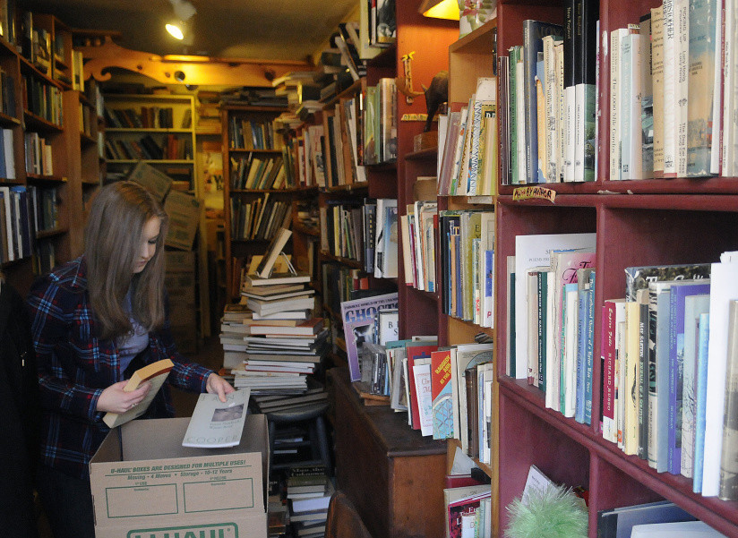 Deni Merrill packs monographs Monday at RiverBooks in Hallowell, which her mother, Edda Briggs Thiele, is closing at the end of the month. The tiny 24-year-old business operated on the honor system, with clients leaving money behind for books they selected.