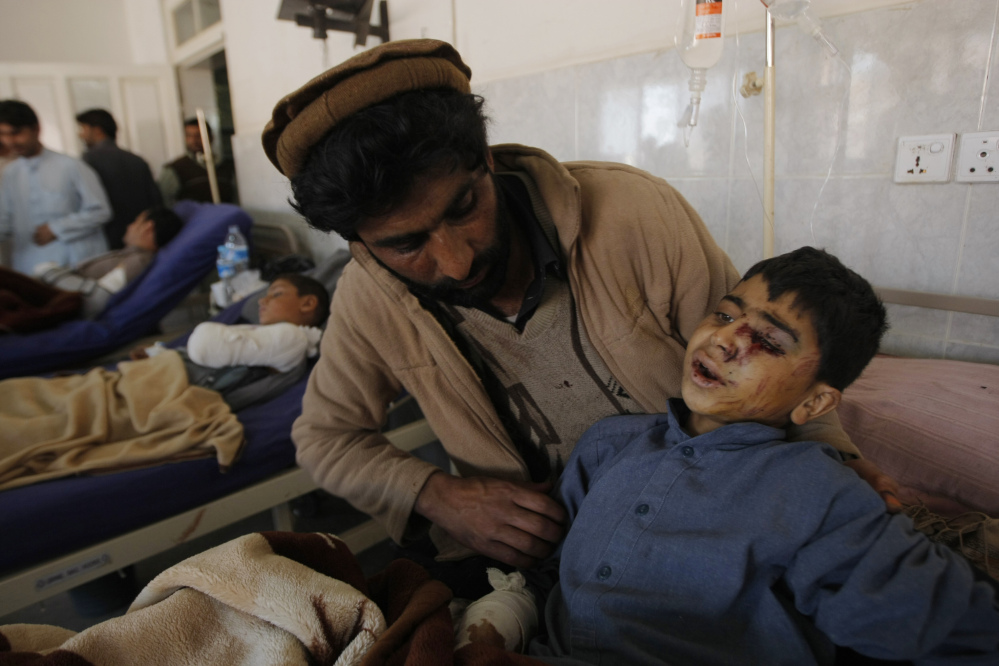 A family member comforts an injured boy at a local hospital in Peshawar, Pakistan, Tuesday, Oct. 27, 2015. Officials say rescuers are struggling to reach quake-stricken regions in Pakistan and Afghanistan. (AP Photo/Mohammad Sajjad)