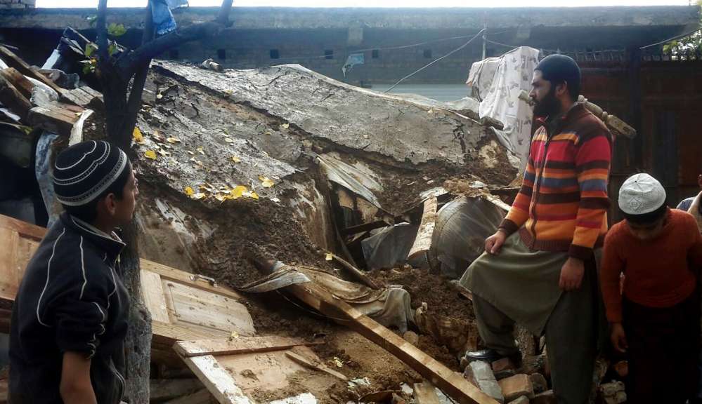 Pakistani residents stand over debris of their house collapsed by an earthquake in Qabal near Mingora in Swat valley, Pakistan, Tuesday, Oct. 27, 2015. Officials say rescuers are struggling to reach quake-stricken regions in Pakistan and Afghanistan. (AP Photo/Sherin Zada)