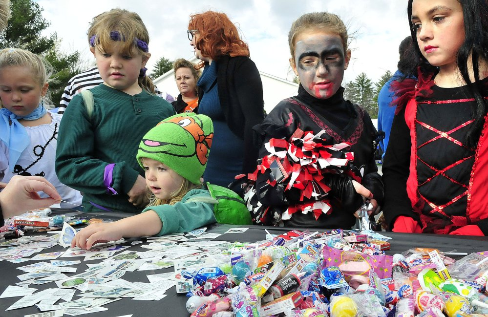 Kids dressed up for Halloween crowd around one of 30 vehicles and owners for candy during a trunk or treat event at the Canaan Elementary school on Oct. 26, 2014.