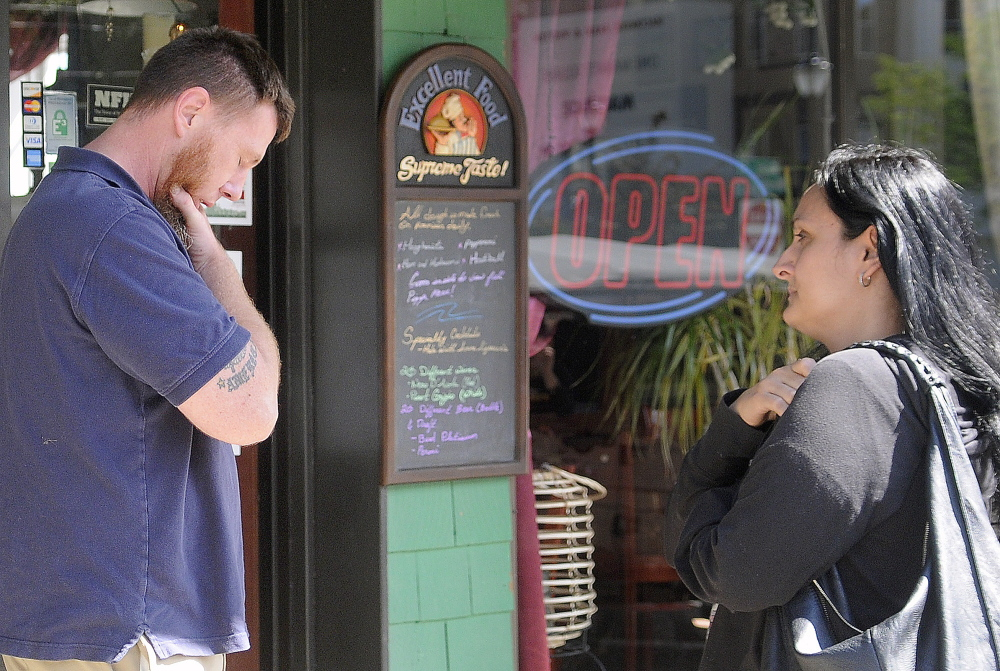 Jason MacFarland speaks with his wife, Helena Gagliano, outside her Augusta restaurant moments after a health inspector visited the Water Street business on Aug. 12. The building that houses the Italian restaurant was closed due to code issues, shutting the restaurant.
