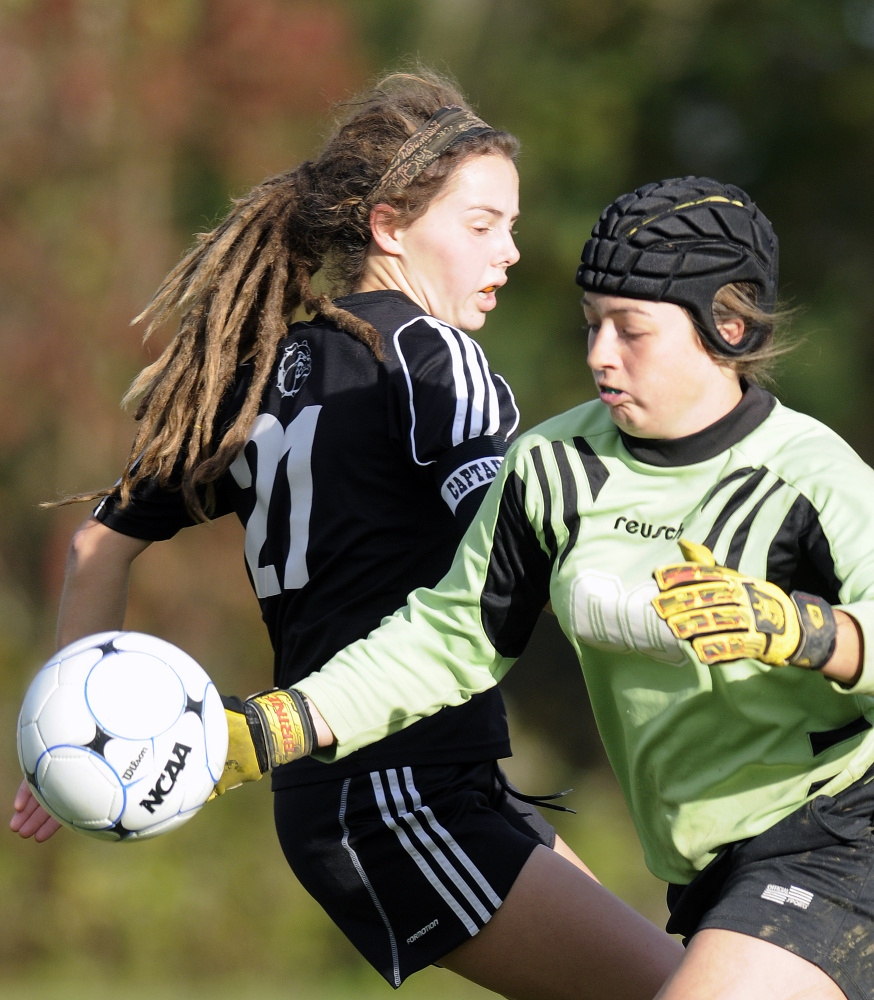 Staff photo by Andy Molloy   Hall-Dale High School's Signe Lynch, left, chases a shot that Monmouth keeper Mikayla Cameron knocked away during a Class C South quarterfinal game Tuesday afternoon.
