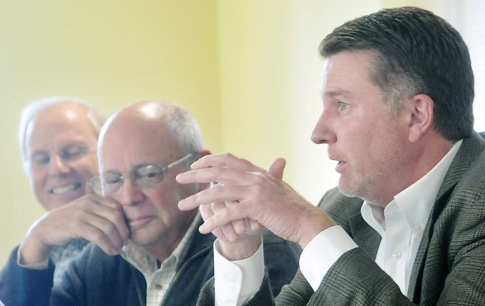 Patrick Keliher, right, commissioner of the Department of Marine Resources, announces Tuesday that Gov. Paul LePage authorized the release of some funds for the Land for Maine's Future program during a board meeting of the agency in Augusta. Keliher sits on the board with Jim Norris, left, and William Vail, second from left.