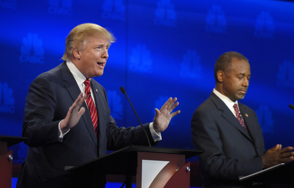 Donald Trump makes a point as Ben Carson listens during the early going in Wednesday night's debate. The two are the front-runners in the polls.