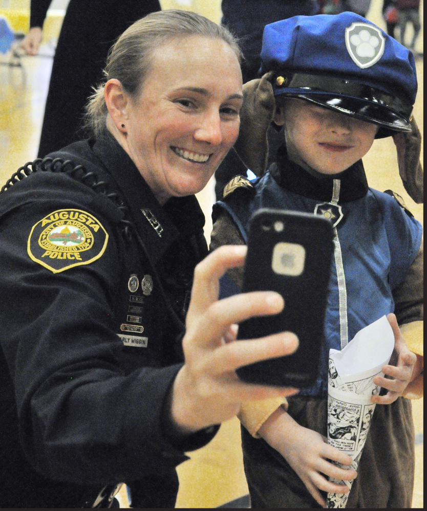 Augusta Police Department School Resource Officer Carly Wiggin takes a photo with Cole Giuffrida who is wearing a Paw Patrol costume during a Lights on After School event last week at the Kennebec Valley YMCA in Augusta. Wiggin, who is stationed at Cony High School, also visits other schools throughout the Augusta system as she works to build relationships with students.